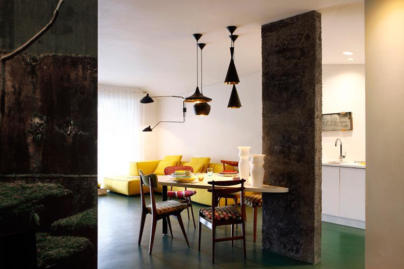 被放在承重墙边的餐椅图案丰富,黑色磨砂吊灯和水泥墙又多了一些工业气氛。
