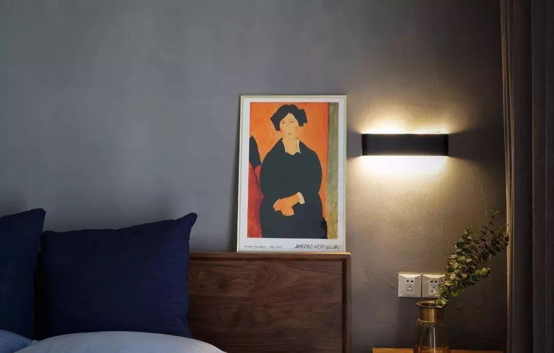 暖色调装饰画与暖光壁灯,提亮主卧空间。