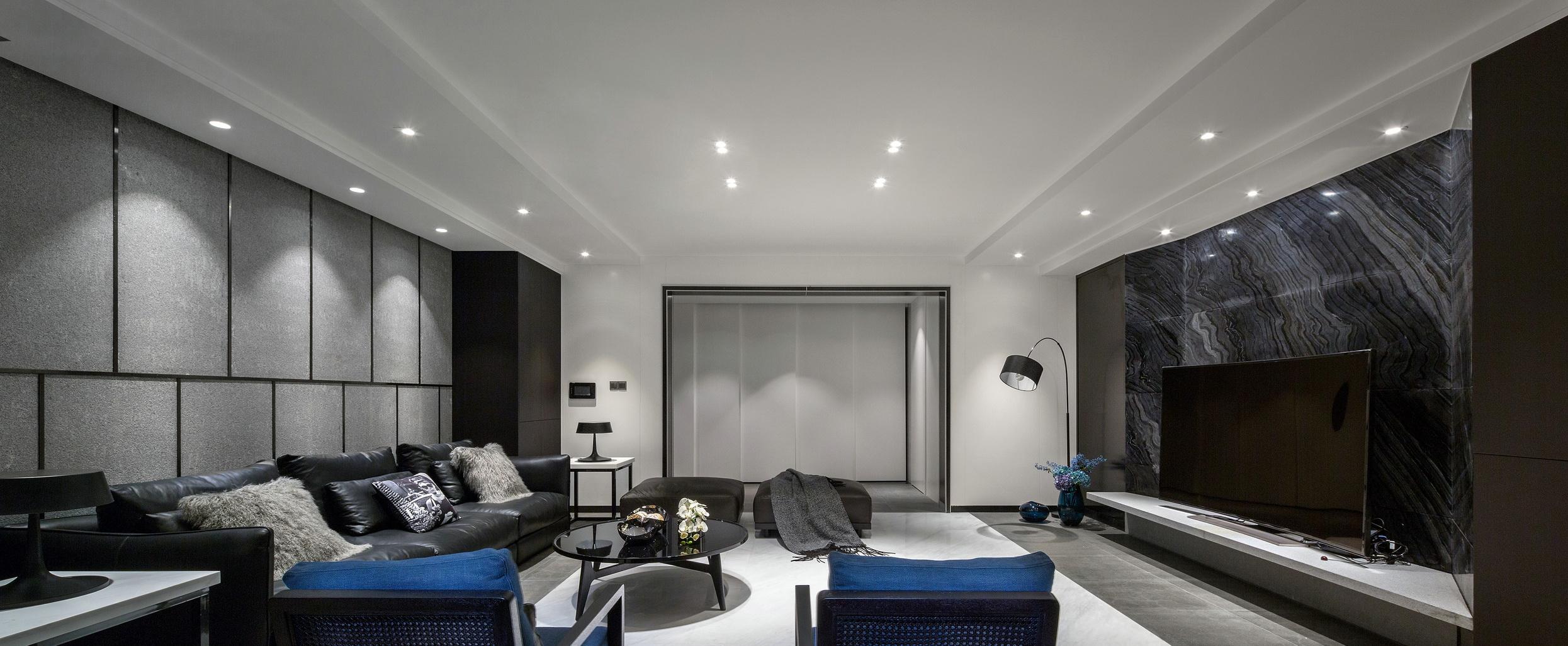 客厅的顶面以精美的吊顶设计,整个墙面以灰白黑组成简单华丽