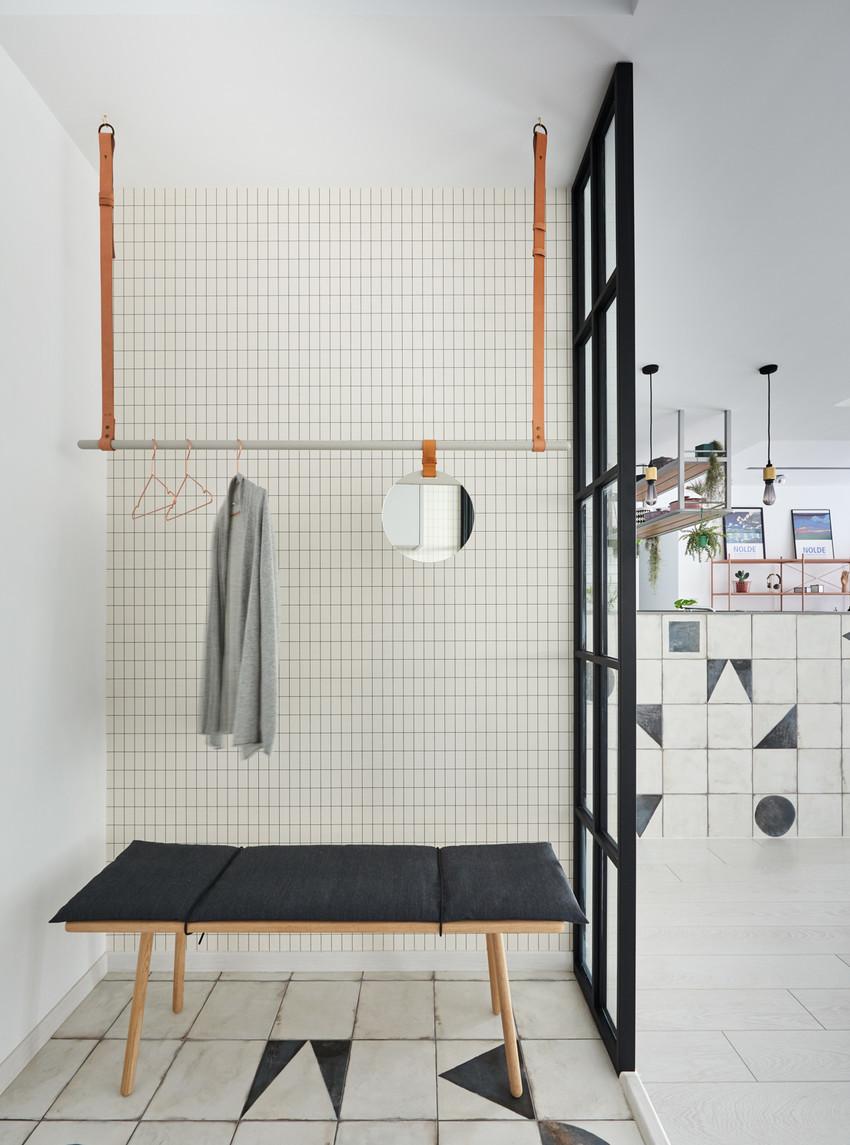 玄关另一侧简单设计了挂衣架和换鞋凳,小方格壁纸满是小清新的味道。