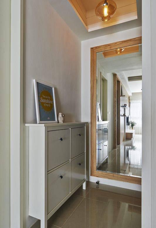 木质框定的大片穿衣镜面于玄关处有效延续采光,预告空间的材质表现,隐藏电箱的位置。
