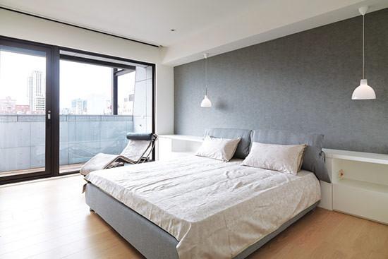 延续阳台的视觉效果,主卧墙面选择清水模质感的壁纸。
