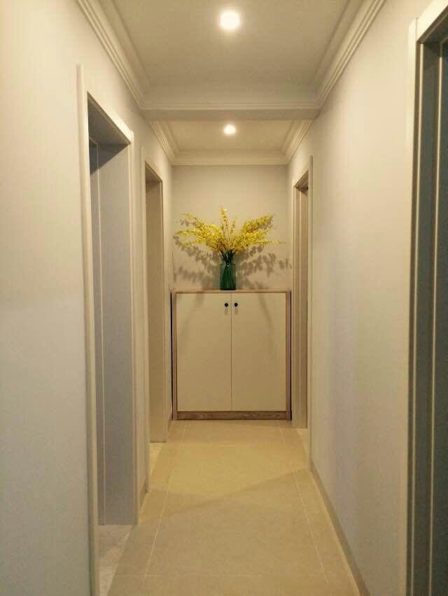走廊尽头,白色与原木色搭配的橱柜,清晰的木纹,极富质感。盛开的装饰植物,充满春天的气息。