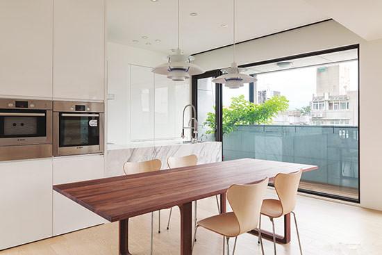 客厅和餐厨均为开放式,采用长沙发做自然的隔断,中岛背板为银弧大理石,厨具则搭配白色钢琴烤漆展现高质感