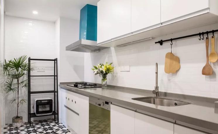 厨房墙面与橱柜都选用了白色,干净亮堂。地面铺设了小花砖,增添一份精致的味道。