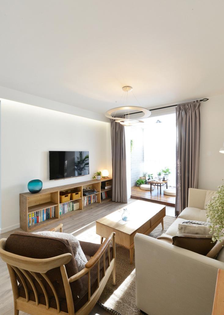 宽敞的客厅用原木家具隔离出空间,米色的布艺沙发把整体的情调变得小资清雅。