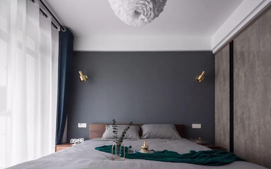 床头金色的壁灯,点亮空间,为它体色不少。衣柜门采用的仿水泥设计非常有个性。