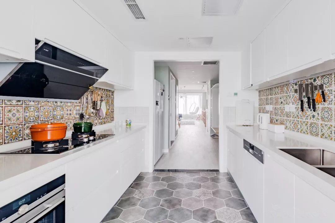 厨房大面积的白色、灰色延续了整体风格的清冷基调,地面六角形仿水泥地砖和屋外白色木地板过度自然。