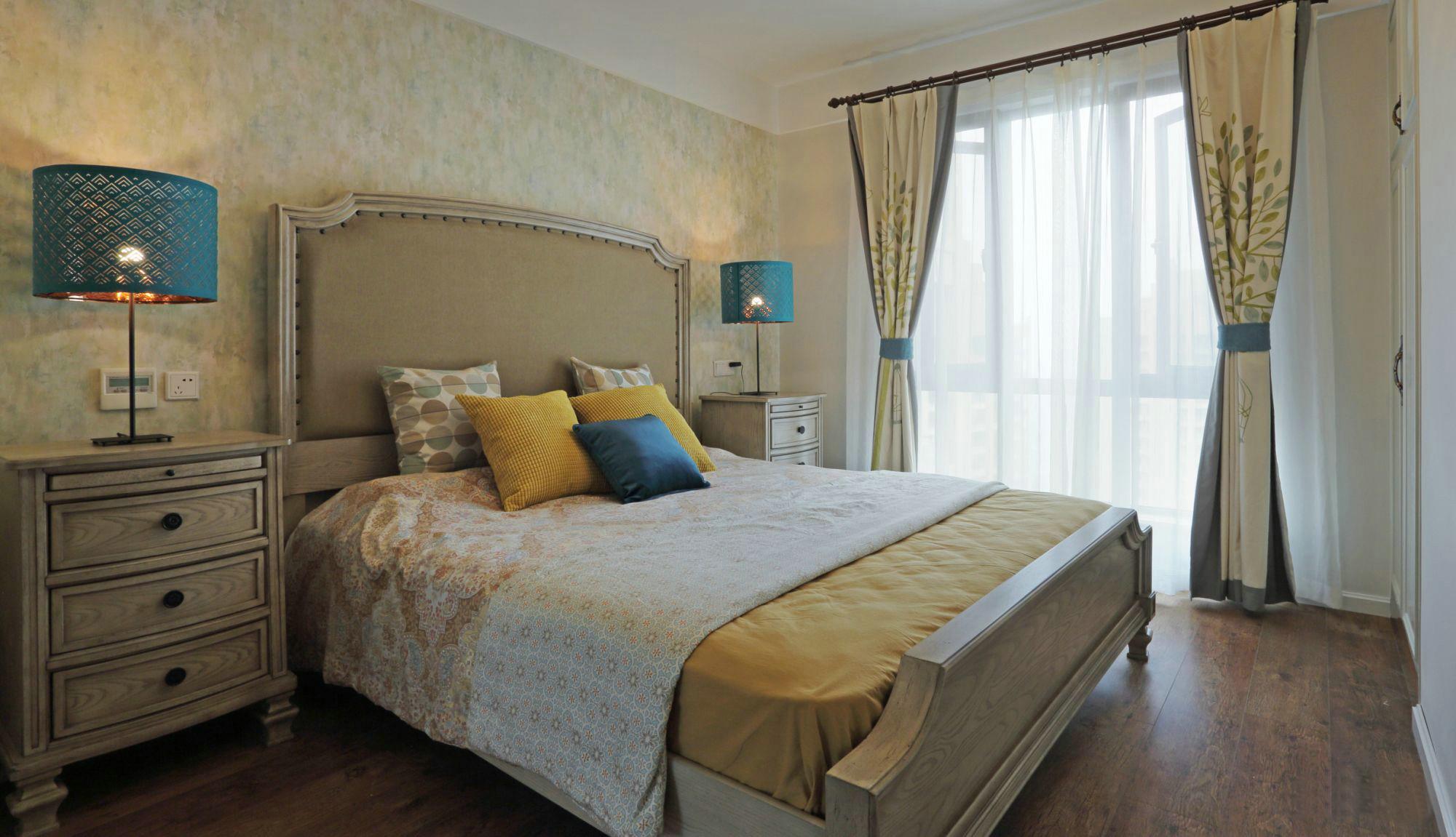 椭圆形的蓝色罩灯为卧室增加了一些亮色。