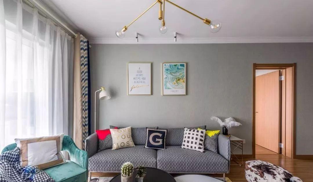 橄榄绿壁纸墙面点缀装饰画,尼摩家的灰色压纹沙发提升了客厅的格调。
