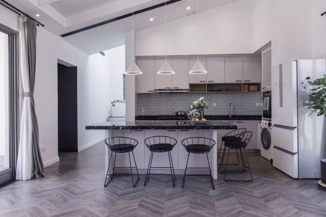 客厅的另一端有一个开放式厨房,中间的餐桌也兼具岛台功能,岛台内还设计了内嵌式电磁炉,满足待客需求。