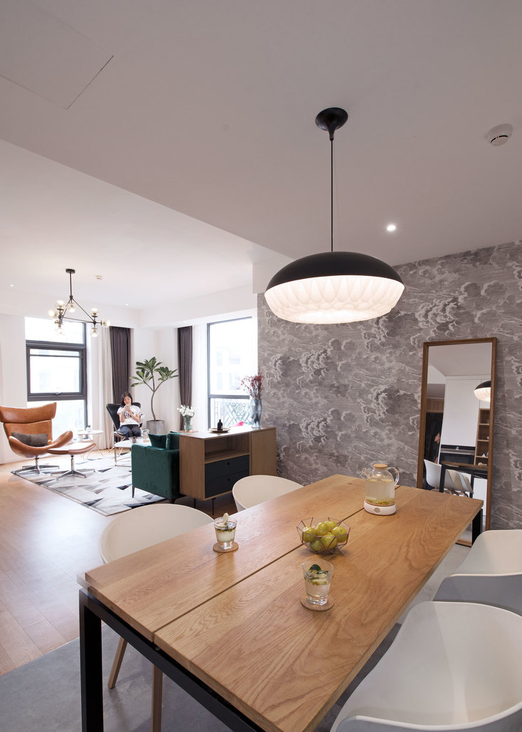 餐厅的设计很经典,温馨的木质餐桌和白色餐椅,搭配黑色精致吊灯,让家的温馨蔓延。