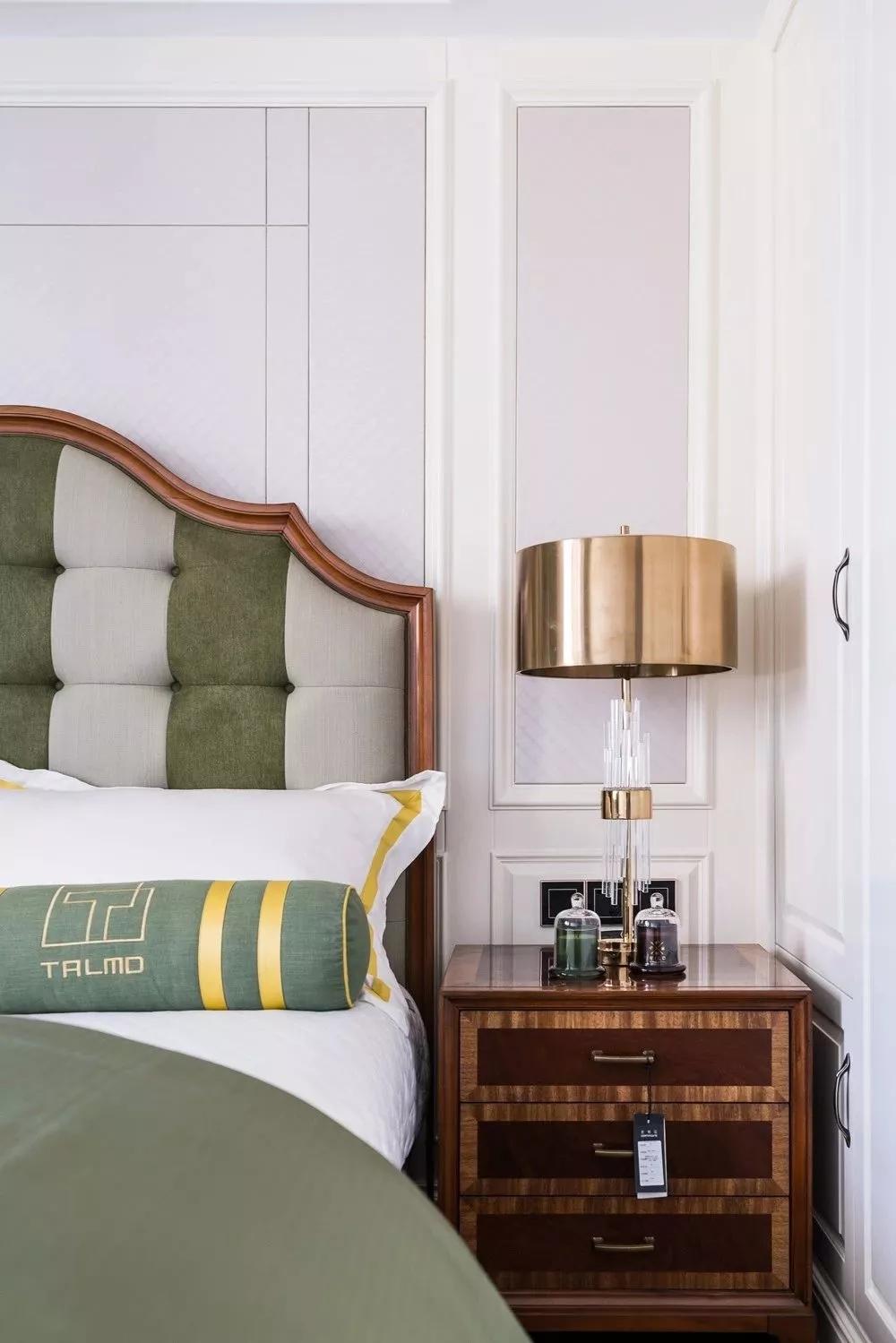 次卧选用绿白相间的床品,金色台灯非常有质感。