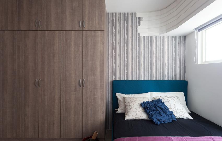 一床一柜构成简易的睡眠空间,曲线造型的天花板,缓解了次卧的单调感。