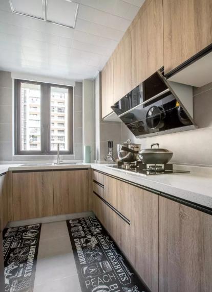 厨房以U型布置,提高空间使用率,整体通铺水泥色瓷砖,搭配木纹柜门,简单轻盈。