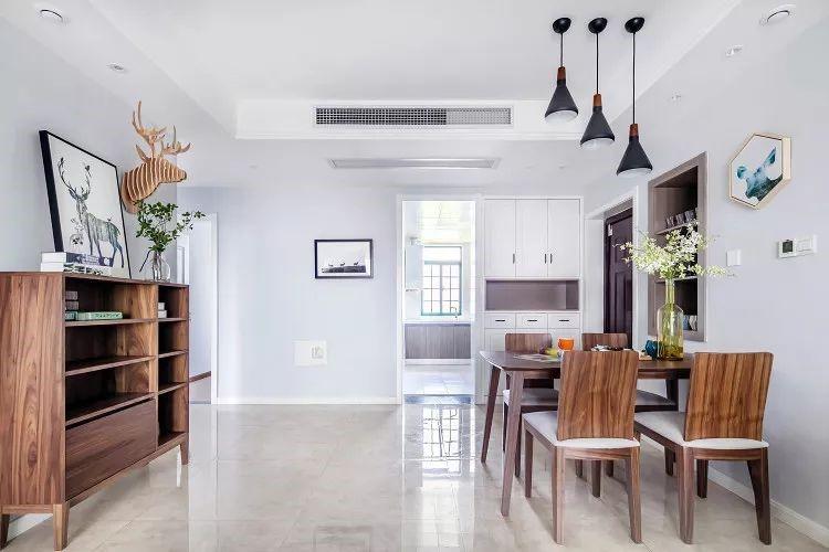客厅望向餐厅方向,餐桌对面是一个实木边柜,上面是鹿元素的装饰画和装饰品,充满艺术感。