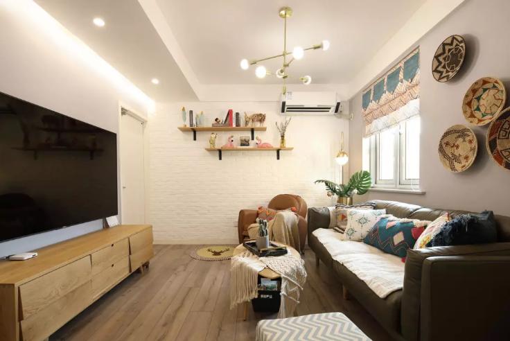 客厅墙面以白色为主,简约精致的小圆形集合吊灯,墙面上定制的两层隔板,做为装饰收纳。