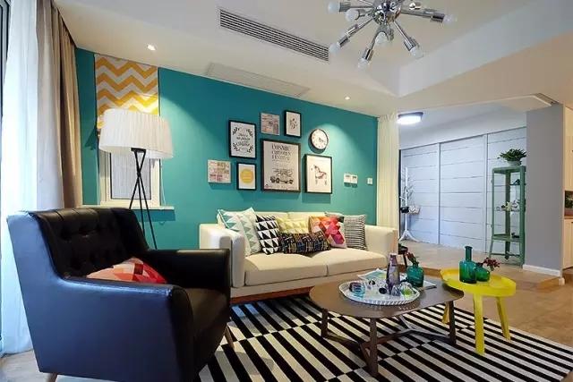 客厅的主色调是蓝、白、黑、黄,四种颜色交织,用一些彩色的抱枕打造趣味。