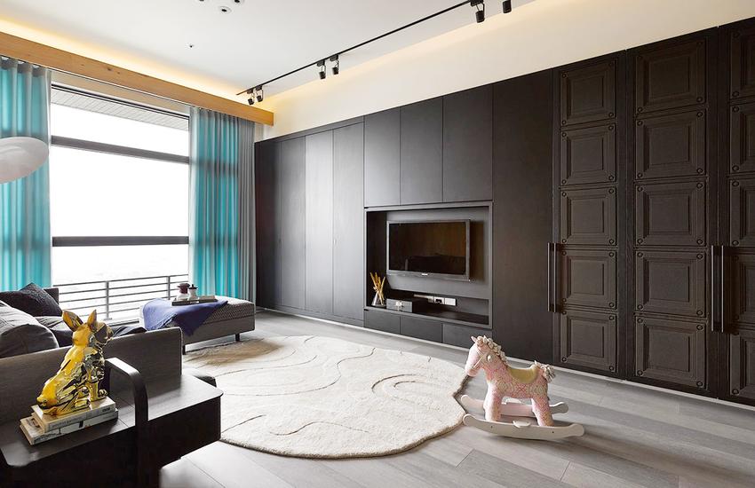 整面背景墙刷成黑色,房主个性彰显无遗,一张白色地毯和粉色木马,又让空间不会过于冷酷。