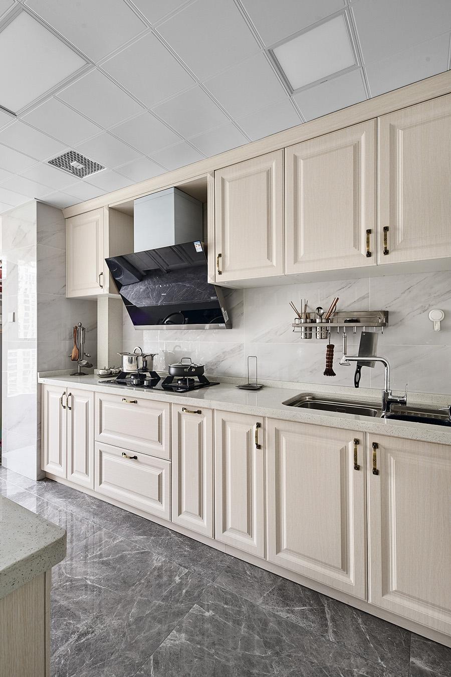 厨房呈现一字型设计,整体以白色橱柜为主调,在深色大理石地板的烘托中倍显优雅。