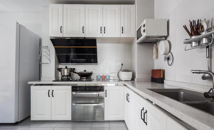 厨房地面通铺灰色瓷砖,立面浅色瓷砖搭配白色橱柜,灰色麻点台面耐脏易打理。