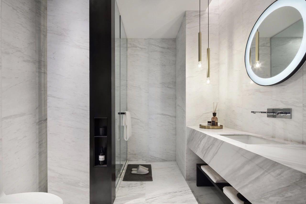 衛生間采用白色大理石鋪貼,通透幹淨,洗手台照明設計層次分明,精致感強。