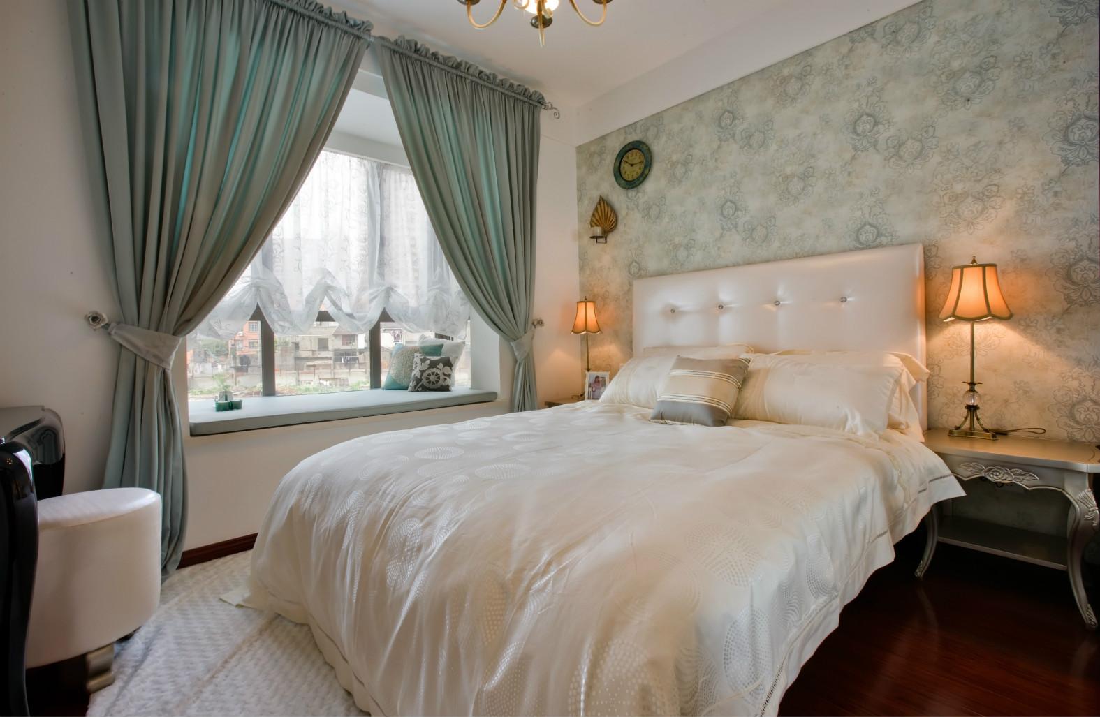 主卧室延伸整体的木地板,床头背景是花色的,点缀两盏壁灯,画面十分好看