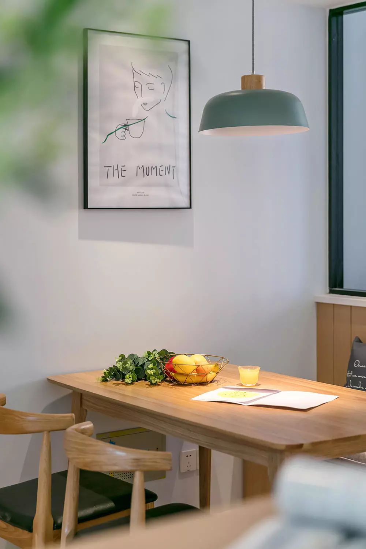 一张原木餐桌搭配复古吊灯,背景装饰一幅简框画,就餐氛围自然温馨。