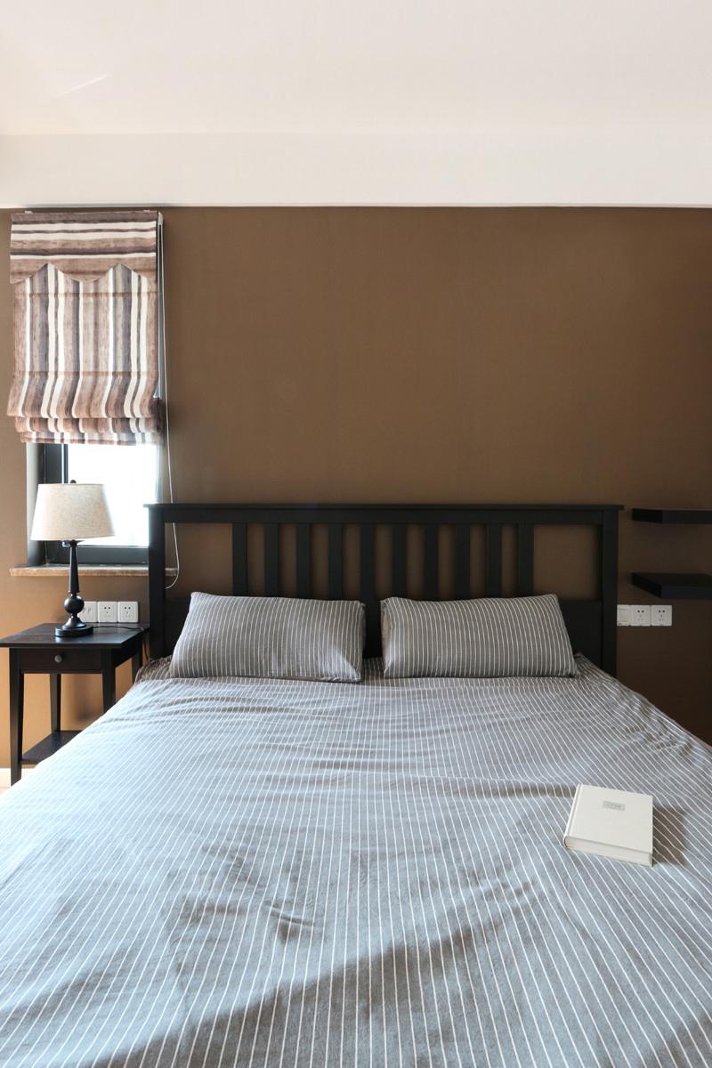 卧室黑色的床榻,带着现代风格,直角线角清晰,简单的而显得冷清。