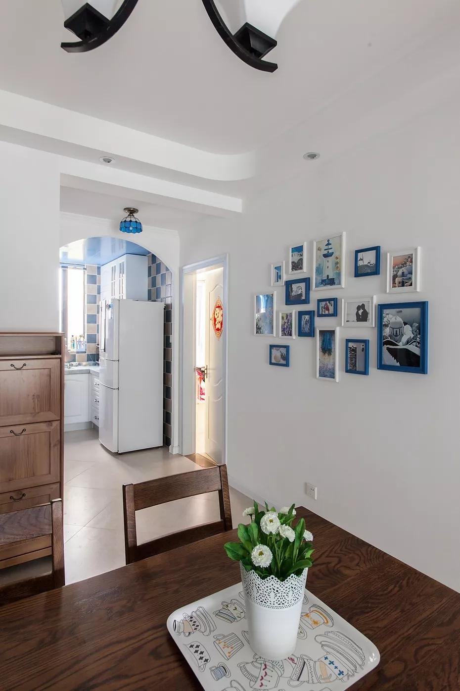 厨房和餐厅走廊的墙面上摆设了照片墙,都是用了蓝色和白色相框,自然清新。