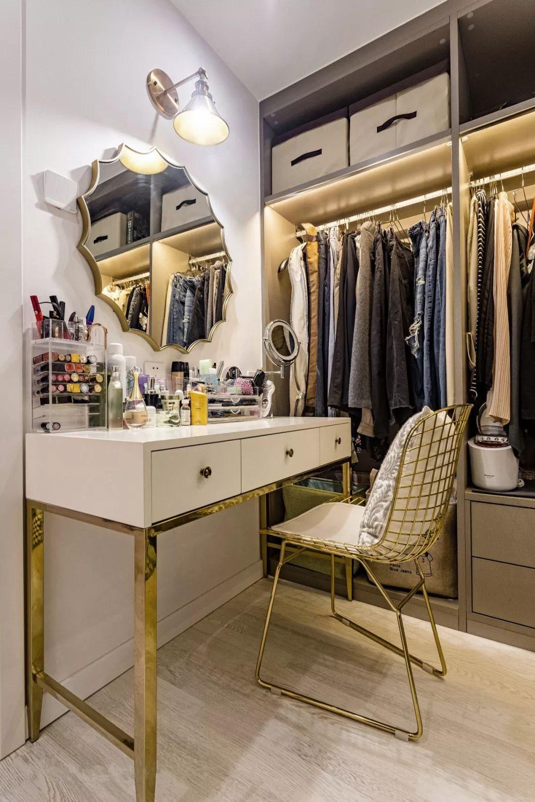 灰布纹板的衣帽柜配金色镶边的梳妆台,一暗一亮。衣柜的层板上也预留了灯带,避免取放衣物时背光。