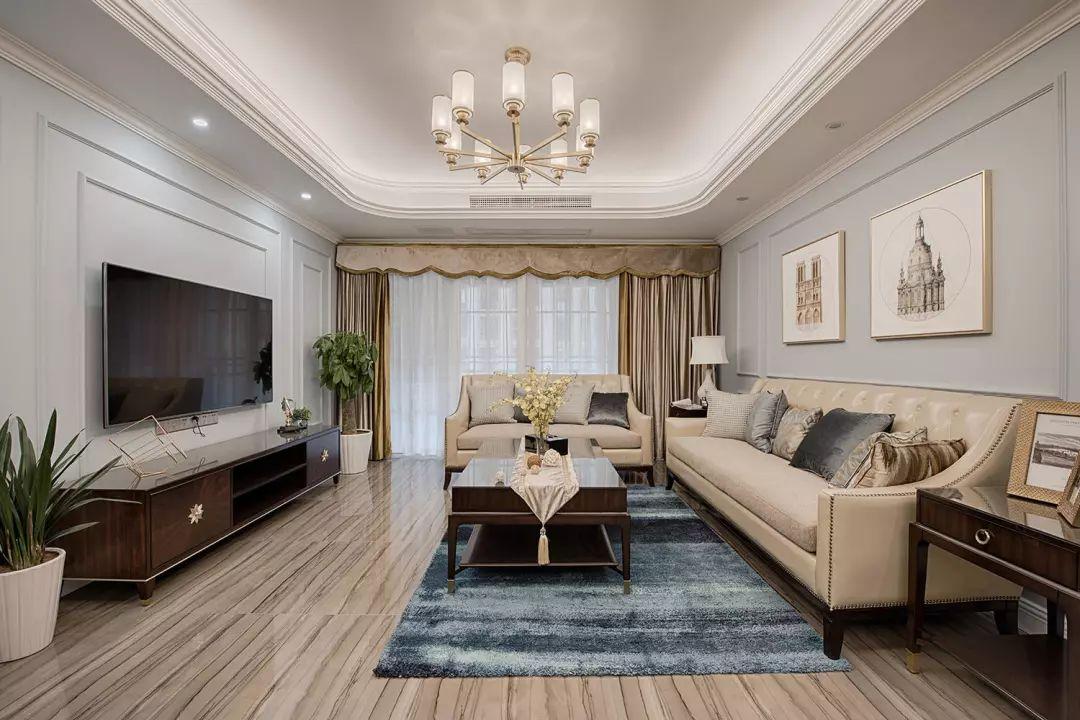 客厅整体以浅蓝灰色为主调,搭配米色家具与金色元素,空间层次丰富。