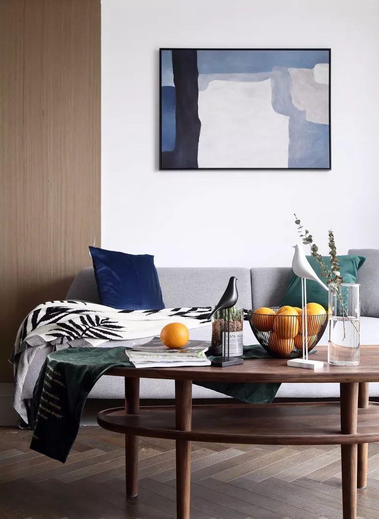 留白的沙发背景搭配一副简单的线条画,木色的茶几也迎合了地板的色调,体现了整体性。