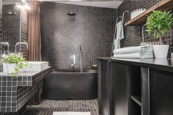 黑色调的洗浴室慢了个性,马赛克小方砖让空间充满张力。