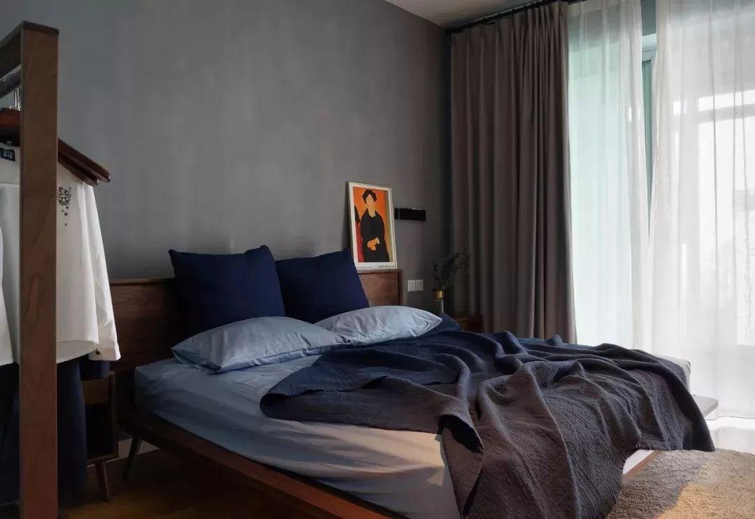 主卧整面水泥墙作床背景,搭配深木色胡桃木家具,营造安静惬意的氛围。