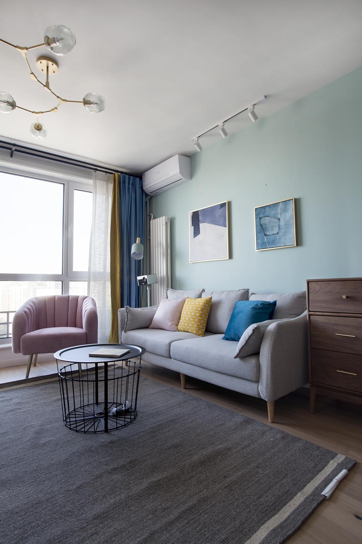 客厅墙面以淡绿色为主,原木色的地砖搭配灰色布艺沙发,局部使用亮色点缀。