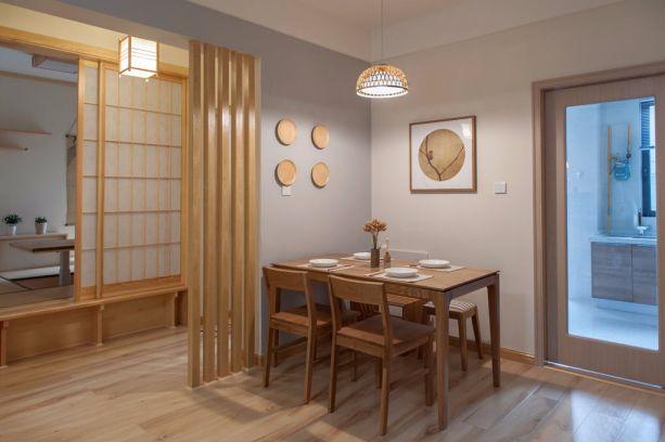 餐厅设计中客厅一角,木质桌椅与居室整体统一,墙面的禅意配饰提升了整个家的品味。