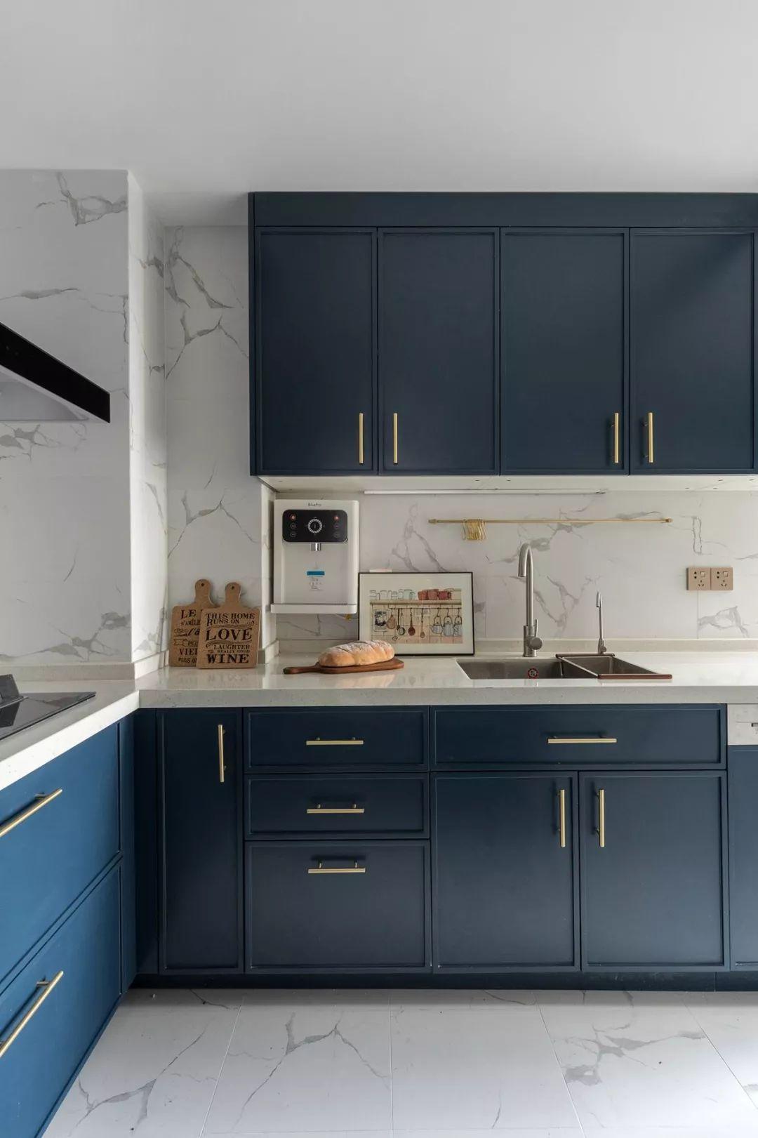 厨房采用L型设计,操作便捷,浅色地砖+墙砖的基础上,搭配深蓝色橱柜,雅致又有档次。