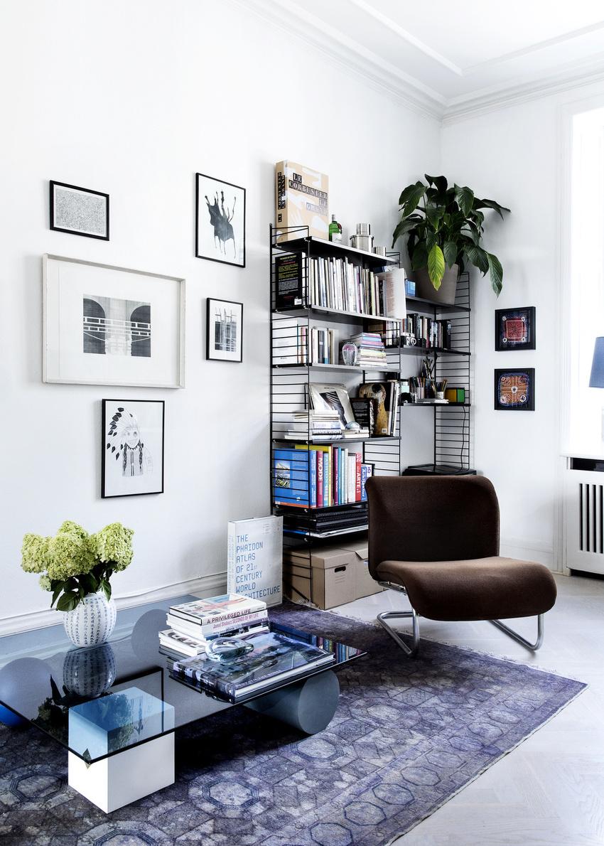 沙发对面的墙角是迷你阅读区,简易的书架,线条感十足,收纳能力也不可小觑。