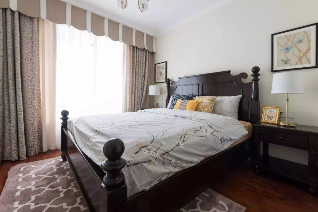 主卧地面通铺木质地板,搭配深咖色实木大床,整个空间氛围沉稳大气。