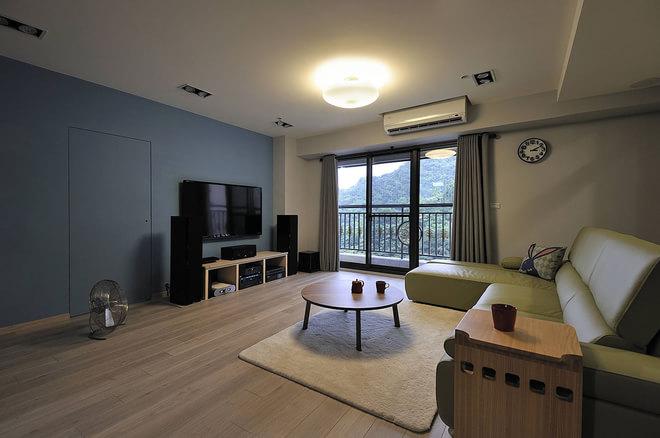 沙发对面的电视背景墙实力深蓝色的乳胶漆刷至而成,电视下面则是放置着简约线条的视听柜设计,很是简约别致