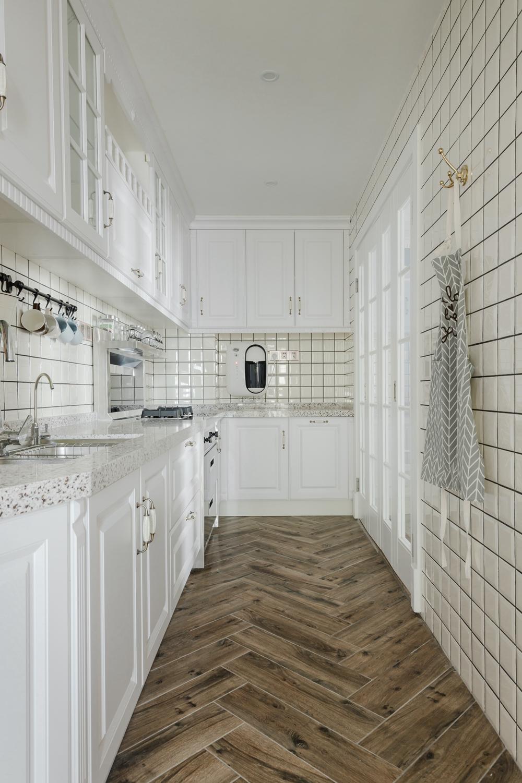 厨房空间规划巧妙,主题以白色为基础,原木地板在其中散发出质朴气息。