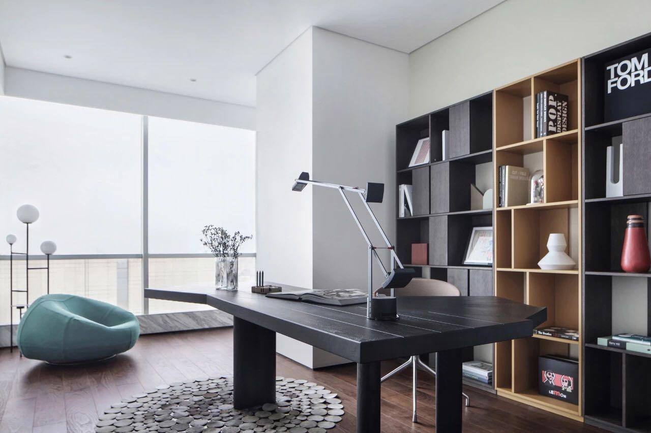 書房淺色背景牆、黑色書桌以及木質書櫃相互搭配,空間顯得大氣簡約。