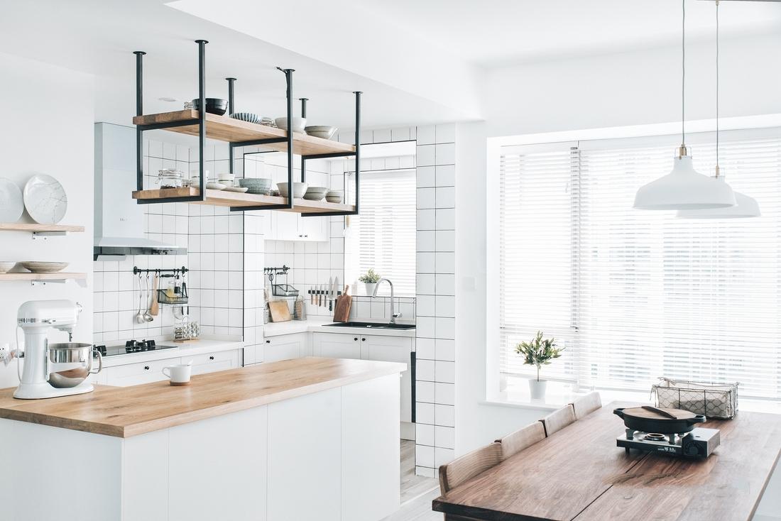 全开放厨房,餐桌为了满足聚会需求因此尺寸较大。墙壁的白色与餐桌的原木色结合,干净而整洁