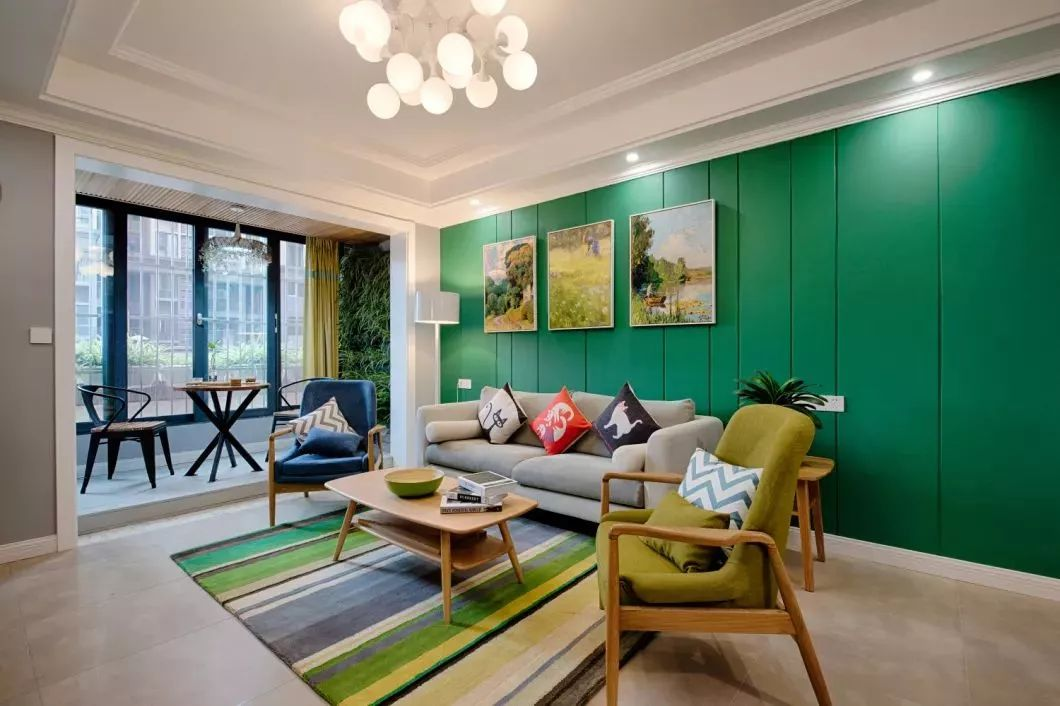 客厅和阳台直接也没有做隔断,沙发背景墙和植物墙相互呼应,浅灰色的布艺沙发搭配色彩斑斓的彩色地毯。