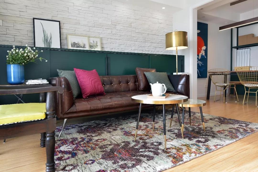 客厅采用大面积墨绿色的橱柜,让人感受到复古唯美的生活氛围;咖色沙发大胆搭配各色抱枕,反而衬出优雅之美