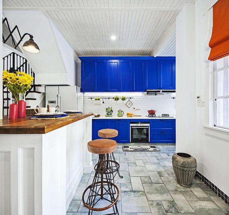 另一边直接与开放式厨房相连,与厨房融为一体,在宝蓝色的橱柜旁,哪怕是家常菜也变得浪漫起来。