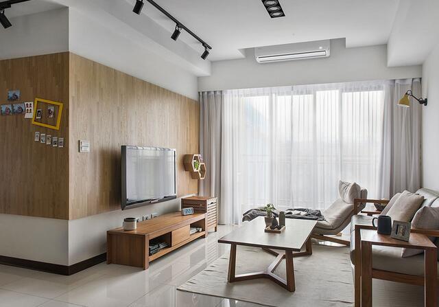选择温润木质元素作为电视主墙,并延伸至廊道壁面,转为纪录一家人生活点滴的相片墙。