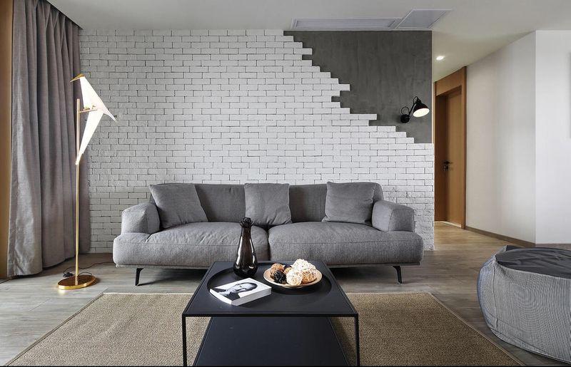 深灰色的沙发和刷白的裸露砖墙绝配,加上右上角空出来的水泥,共同在安静简洁的空间里营造出一种粗犷的感觉
