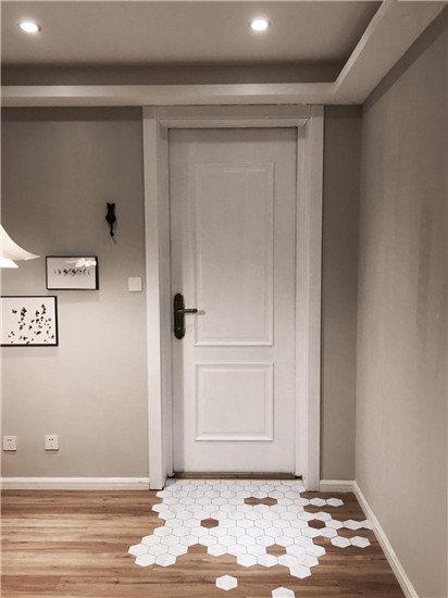 进门处放置鞋柜,只在进门左手边的墙面安装了两个二黑木作的黑胡桃木挂衣架,配上黄铜的挂衣钩很有气质。